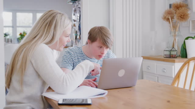Downs Syndrome Man Sitting With Female Home Tutor Using Laptop For Lesson At Home Young man with Downs Syndrome working with female home tutor on laptop at home - shot in slow motion disability stock videos & royalty-free footage