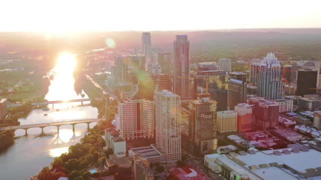 AERIAL Downtown Austin with Colorado River shining in the setting sun