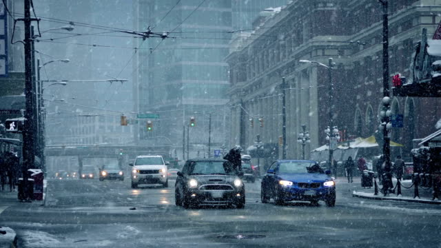 Downtown City Road In Snowfall Cars and cyclist on city road in winter snowfall vancouver canada stock videos & royalty-free footage