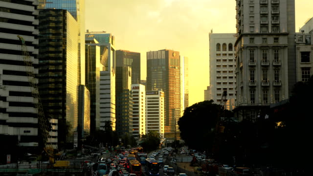 Downtown Jakarta business district city scene at sunset with flowing traffic 4k video Downtown Jakarta business district city scene at sunset with flowing traffic 4k video jakarta stock videos & royalty-free footage