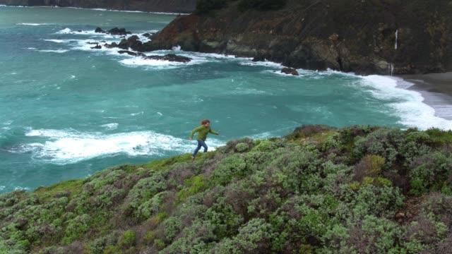nedåtlutande antenn av kvinna vandring i big sur - kustlinje bildbanksvideor och videomaterial från bakom kulisserna