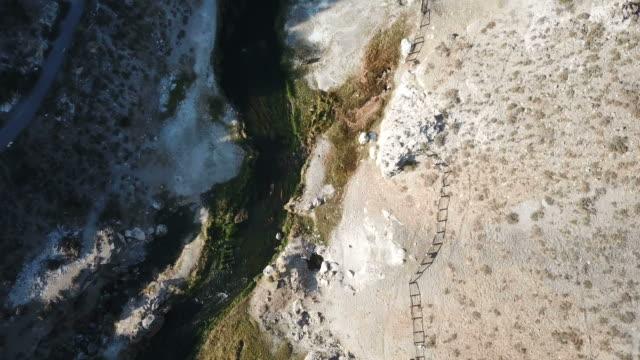 downward view of hot springs in ravine in wilderness - дикая местность стоковые видео и кадры b-roll