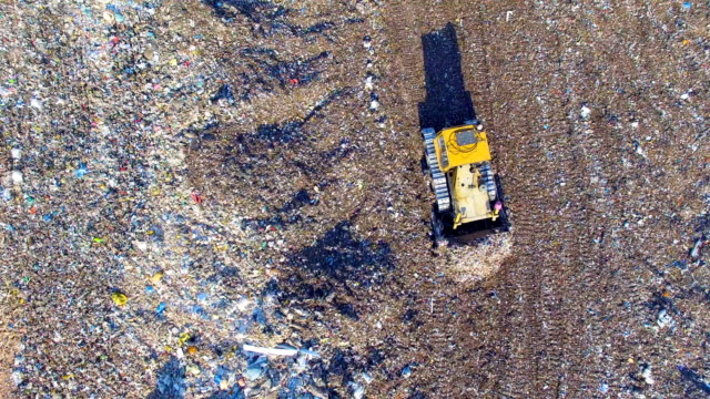 4K. Dozer, bulldozer working at the garbage dump. Directly from above. Aerial shot. video