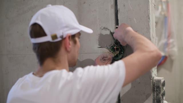vídeos y material grabado en eventos de stock de borrador de trabajo sin trabajo en el apartamento. el maestro hace reparaciones - descarga eléctrica