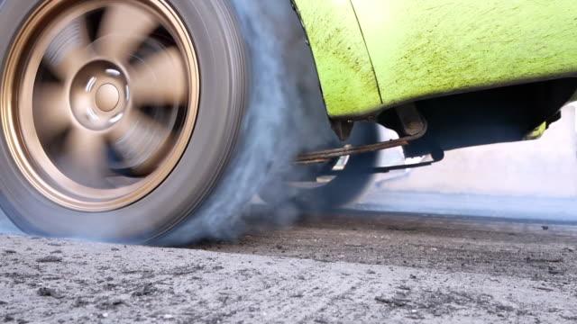 dra bildäck gör värma upp med rök, car racing utbrändhet gummi av dess däck inför loppet. - wheel black background bildbanksvideor och videomaterial från bakom kulisserna