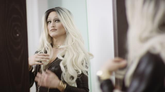 stockvideo's en b-roll-footage met drag queen zichzelf in de spiegel te controleren - drag queen