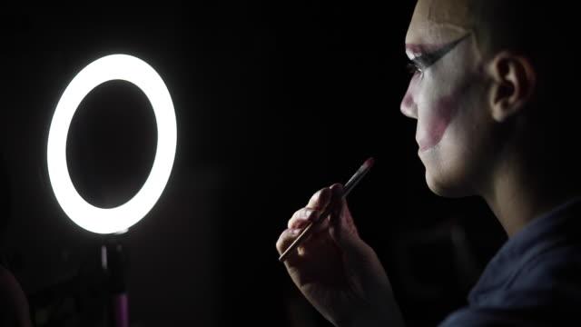 stockvideo's en b-roll-footage met drag queen zetten rode lippenstift in donkere kamer - toneelschmink