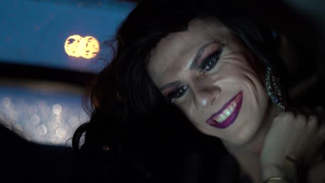 stockvideo's en b-roll-footage met drag queen met behulp van mobiele op auto - drag queen
