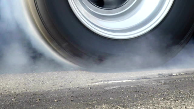 Drag racing car burns rubber off its tire for the race video