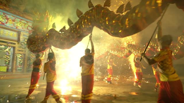 vídeos de stock, filmes e b-roll de dança do dragão mostrar com fogo de artifício no festival de ano novo chinês, no meio da noite. - arte, cultura e espetáculo