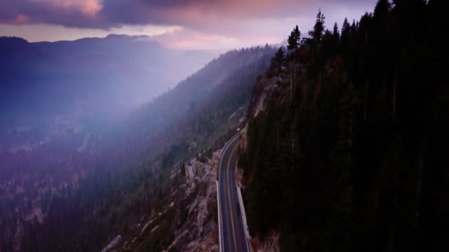 Dramatic Aerial View of Highway in Sierra Nevada, CA Drone shot flying high above U.S. Route 50 as it crosses the Sierra Nevada in California, between Sacramento and Lake Tahoe. The camera follows the road as it climbs the mountainside, tilting to look straight down. western usa stock videos & royalty-free footage