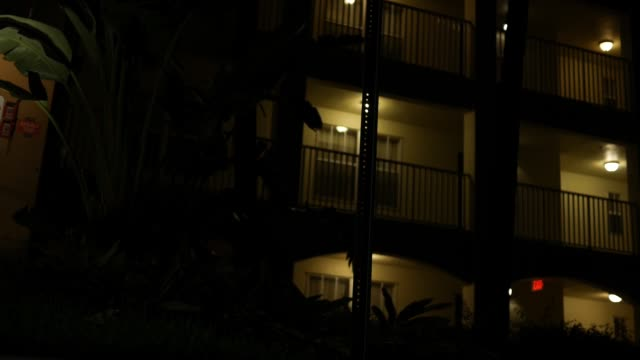 A dramatic apartment complex locked down angle as seen from low angle locked down camera - suspense style shot. - vídeo