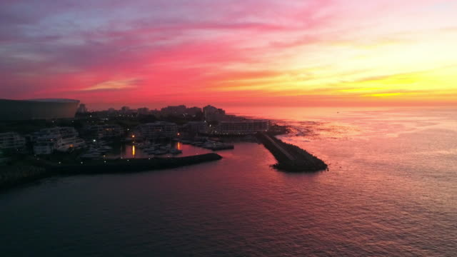 Dramatic Cape Town sunset Aerial shot of camera flying sideways looking at Granger Bay harbor in Cape Town as the sun sets over the horizon cape town stock videos & royalty-free footage