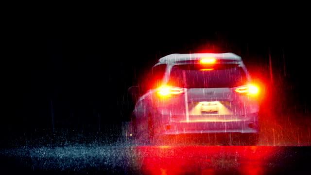 stockvideo's en b-roll-footage met dramatische auto rijdt door regen met remlichten - mist donker auto