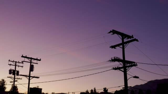 Dramatic Sky with Power Lines - Drone Video Silhouetted power lines in Montrose California shot with a drone against a beautiful purple sunset sky. high voltage sign stock videos & royalty-free footage