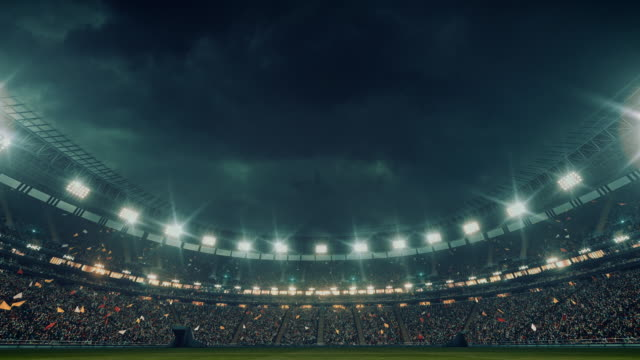 Dramatic soccer stadium full of spectators 4K video: Low angle view of an outdoor soccer stadium or arena full of spectators under a stormy sky. The image has depth of field with the focus on the foreground grass. With intentional lensflares. Full 3d modelled and animated soccer stadium with moving lights floodlit stock videos & royalty-free footage