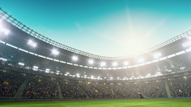 Dramatic soccer stadium full of spectators 4K video: Low angle view of an outdoor soccer stadium or arena full of spectators under a stormy sky. The image has depth of field with the focus on the foreground grass. With intentional lensflares. Full 3d modelled and animated soccer stadium with moving lights floodlight stock videos & royalty-free footage