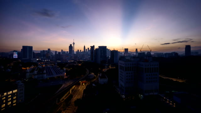 dramatic sunrise at Kuala Lumpur city with sun burst ray. Moving and changing color clouds. video