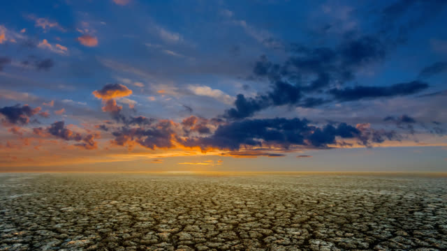 dramatic sunset over a dry saline land in a cracks