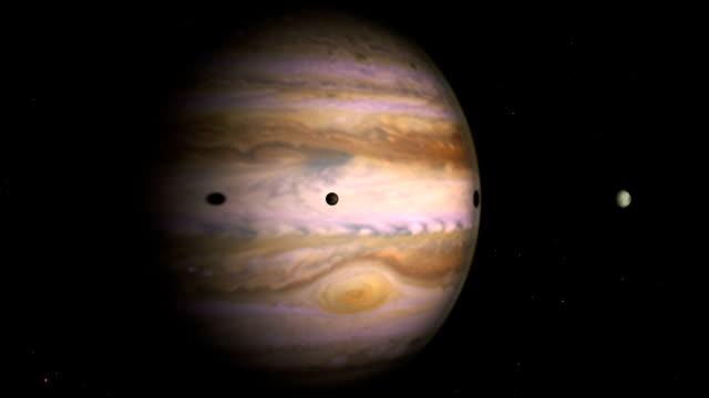 dramatyczny strzał śledzenia jowisza, io i europy, z aktywną atmosferą i wirującymi chmurami - io księżyc filmów i materiałów b-roll