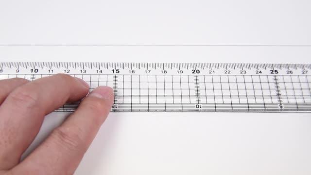 vídeos de stock e filmes b-roll de drawing a line with a ruler and pencil. - reto descrição física