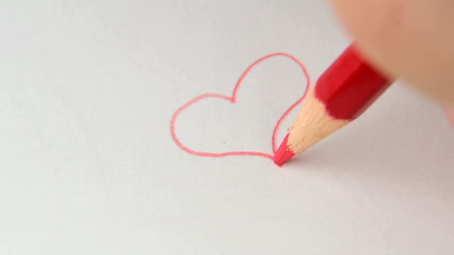 Drawing heart on white drawing paper with red color pencil. artistic concept. video
