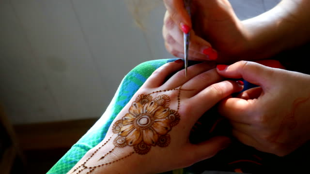 Drawing henna on a female hand. video