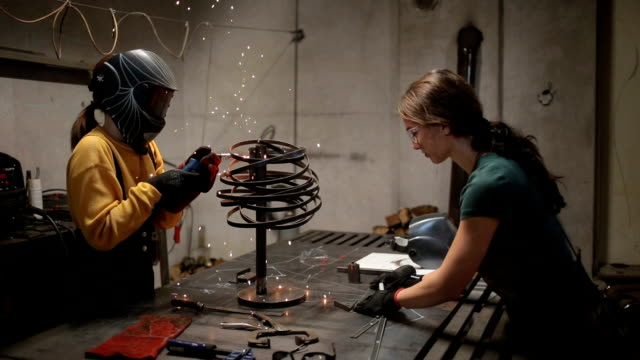 Drawing plans and welding sculptures Young sisters working in their workshop together, welding and cutting things out of metal. independence stock videos & royalty-free footage