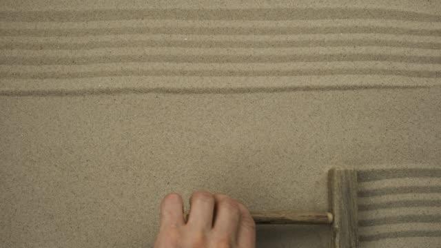 Dessin avec un bâton sur le sable. Lignes droites dans le sable. Dessin symbolique, espace de copie. - Vidéo