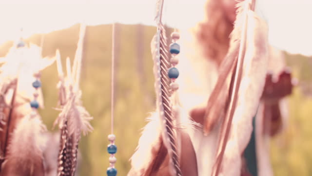 Dream catcher being held up in a natural evening landscape video