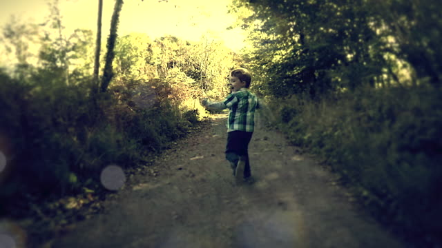 A dream like setting of a young boy laughing and smiling as he runs through the forest in slow motion