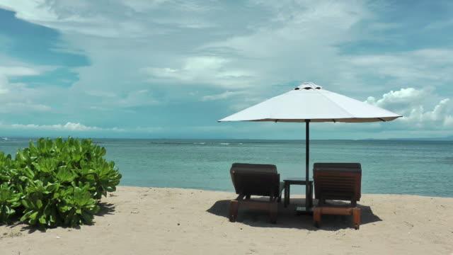 Dream vacation; blue sky,  ochre sand, white beach umbrella video