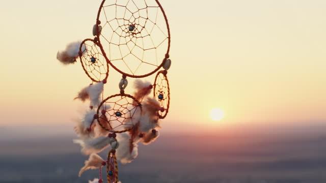 vídeos de stock, filmes e b-roll de o apanhador de sonhos com penas laranjas gira nas montanhas, balançando com vento leve câmera lenta novamente céu azul ao pôr do sol no verão. amuleto estilo boho, estilo indiano. disco brilhante do sol, raios solares - boho