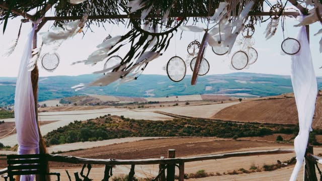 Dreamcatchers blow in the wind. Dreamcatcher hanging in breeze at sunset. Outdoor aisle decoration on countryside. Wedding ceremony.
