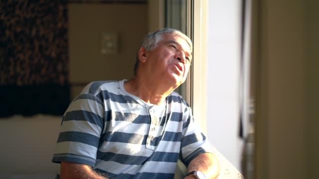 vídeos de stock e filmes b-roll de dreamer senior man looking through window - old men window