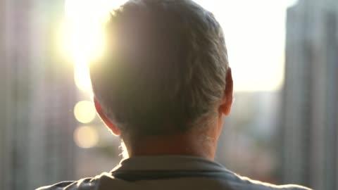 vídeos de stock e filmes b-roll de dreamer senior man looking through window - homens