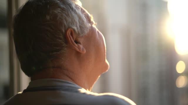 Dreamer senior man looking through window