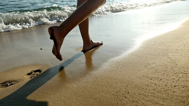 Dreamlike walk with footprint on beach Hd slow motion close-up and rear view video of young woman's wet feet walking naked in soft sand with barefoot down on beautiful sandy golden beach along the Mediterranean sea. Woman stepping step by step during summer sunset at the water's edge and let footprint in sand. Water waves splashing and refreshing the legs. Beautiful day with sunbeams. Carefree vacation in French riviera. Space for copy, camera stabilization video, zoom technique. foot stock videos & royalty-free footage