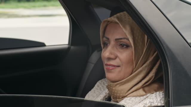 Dreamy Arab woman sitting in back seat video