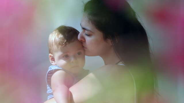 dreamy mother holding baby son surrounded by flower petals - 0 11 mesi video stock e b–roll
