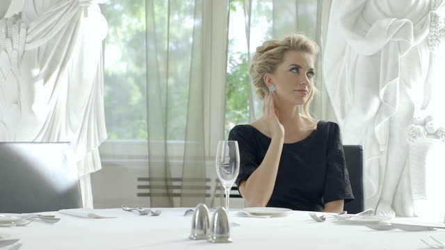 Dreamy young woman waiting for waiter at restaurant table video