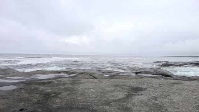 vidéos et rushes de morne ciel au-dessus de rough océan scène au-delà l'estran rocheux - littoral