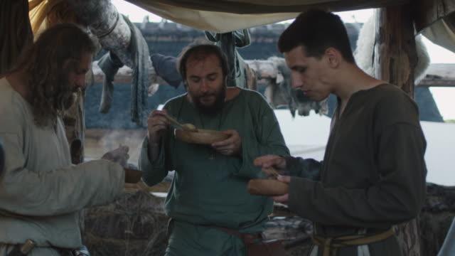 stockvideo's en b-roll-footage met gekleed in middeleeuwse kleding groep mannen eten. leven van civiele mensen op het dorp. middeleeuwse re-enactment. - middeleeuws