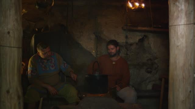 stockvideo's en b-roll-footage met gekleed in middeleeuwse kleding mensen ontspannen, te praten, te drinken en te koken, leven van de burgerbevolking in village. middeleeuwse re-enactment. - middeleeuws