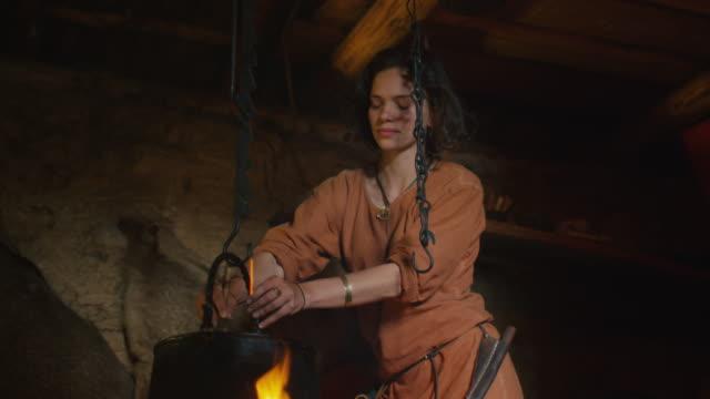 stockvideo's en b-roll-footage met gekleed in middeleeuwse kleding vrouw koken van een maaltijd in brand. leven van de burgerbevolking in village. middeleeuwse re-enactment. - middeleeuws