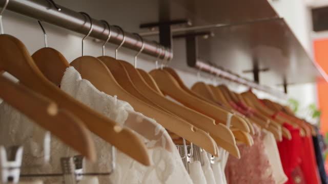 kleider in einem bekleidungsgeschäft - kleid stock-videos und b-roll-filmmaterial