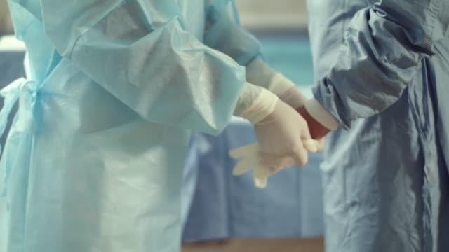 dressing medical gloves. surgery. - vestirsi video stock e b–roll