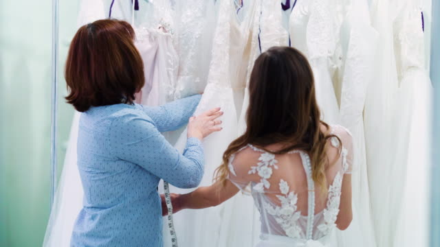 Dressmaker and young bride choosing wedding dresses in salon