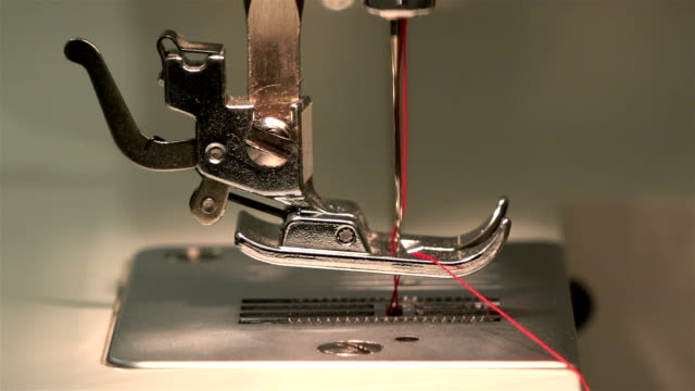 dressmaker down the needle through needle plate and makes a loop for sewing on a sewing machine - cilindro video stock e b–roll