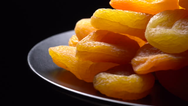 dried apricots. close up.   pile of golden dry apricots in rotation on black background.  organic food, sweet dessert.  dried fruits concept. healthy food concept. - albicocca video stock e b–roll